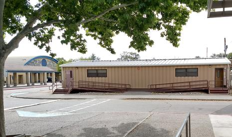 Picture of the Family Center, which is a trailer across the street from the  Fine Arts Building. The door on the right side of the trailer is the one that  leads to the office. The trailer is wheelchair accessible.